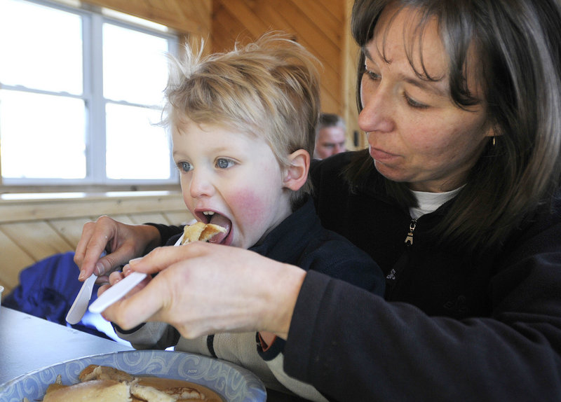 Aaron Pickering, 3, of Kennebunk takes a big bite of a pancake with the help of his mother, Kathy Pickering, during Maine Maple Sunday at Harris Farm in Dayton.