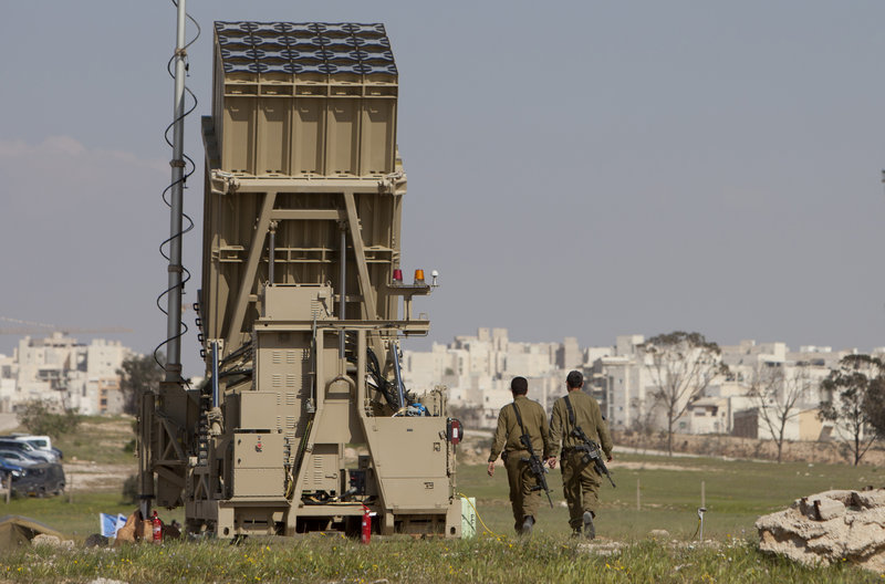Israeli soldiers walk next to the Iron Dome, a new anti-rocket system, near the Israeli city of Beersheba on Sunday. Weeks of stepped-up rocket and mortar attacks have drawn fears of renewed war and led to new calls in Israel for the military to deploy the $200 million anti-rocket system.