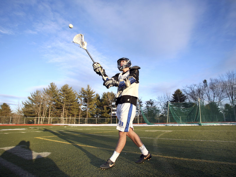 Senior Kyle Groves plays catch during boys lacrosse practice at Yarmouth High on Monday afternoon. Some teams took to their turf fields, while others convened in school gyms until as late as 10 p.m. Monday.