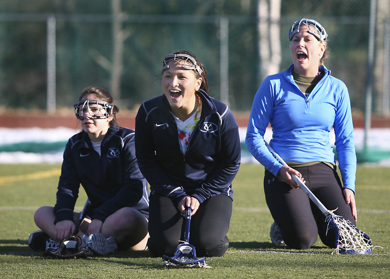 Mo McNaboe, left, senior captain Devin Simsarian, center, and Mariah Lanfer cheer on their Yarmouth High girls' lacrosse teammates during a relay race on the first day of practice Monday at Yarmouth.