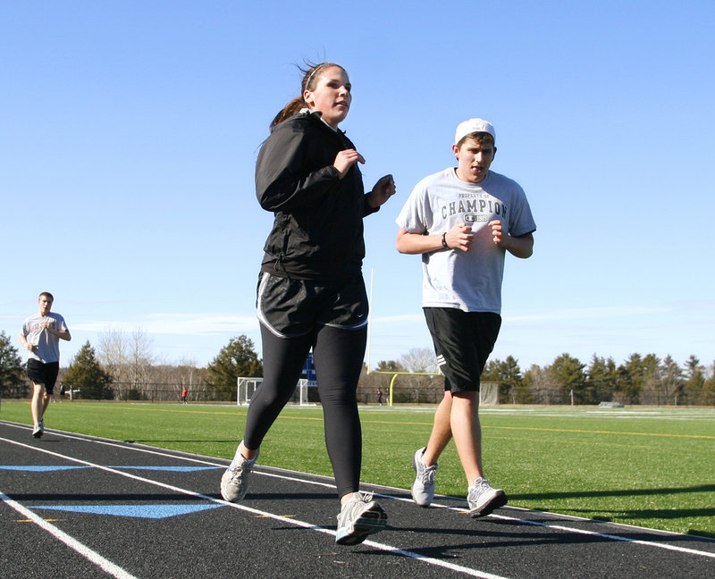 Jenna Serunian and Andrew Kowalsky take a few laps at the track at Falmouth High School as part of the outdoor track team's opening-day practice.