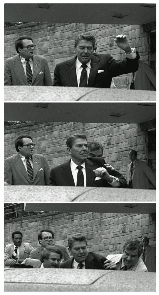 President Reagan waves, then looks up before being shoved into the presidential limousine by Secret Service agents after being shot outside a Washington hotel March 30, 1981.