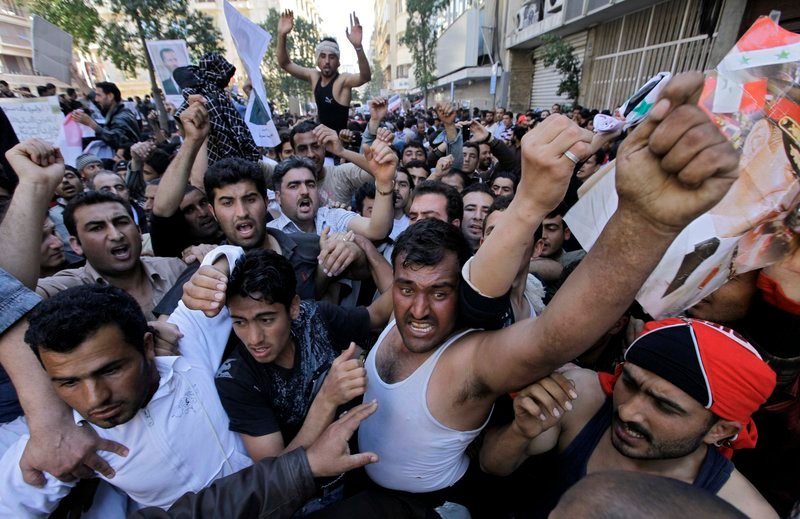 Pro-government protesters shout slogans as they carry pictures of Syrian President Bashar Assad during a sit-in Sunday in front of the Syrian embassy in Beirut.