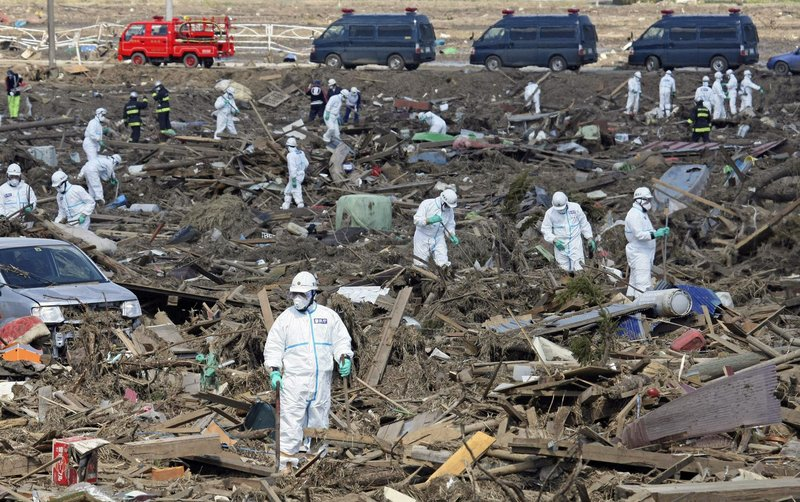 Tokyo Metro Police officers wearing protective suits search for the remains of victims of the giant tsunami triggered by the March 11 earthquake in Minamisoma, Fukushima prefecture, Japan, on Monday.