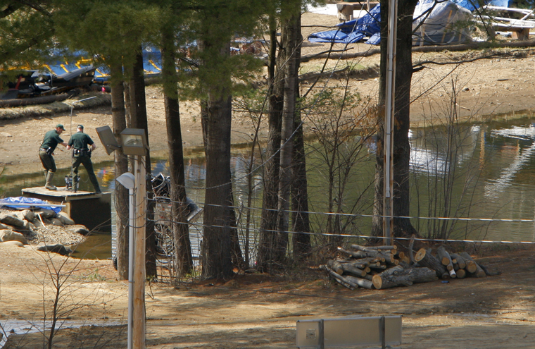 Investigators collect evidence at a snowmaking pond at Mount Cranmore in Conway today.