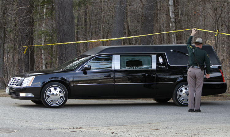 A New Hampshire State Police trooper holds up police tape so a hearse can pass underneath and leave Mount Cranmore in North Conway, N.H, today.