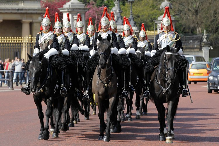 The Blues & Royals of the Household Cavalry Mounted Regiment ride pass Buckingham Palace in London on their way to the Horse Guards Parade, Wednesday, April 6, 2011. The Blues & Royals together with the Life Guards will form a Sovereign's Escort for Queen Elizabeth II and a Captain's Escort for the bride and groom from Westminster Abbey to Buckingham Palace during the royal wedding of Prince William and Kate Middleton on April 29, 2011. (AP Photo/Sang Tan)