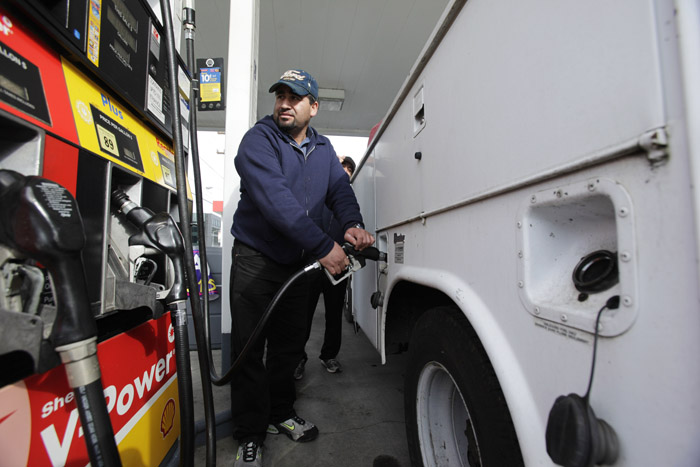 A motorist fills up at a Shell gas station recently in Seattle. The national average for a gallon of gas was $3.88 today.
