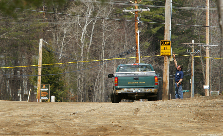 A man lifts police tape to let in a New Hampshire truck to the pond near the base lodge of Mount Cranmore in North Conway that was searched today. The pond, which is used for snowmaking, is near where Krista Dittmeyer's car was found.