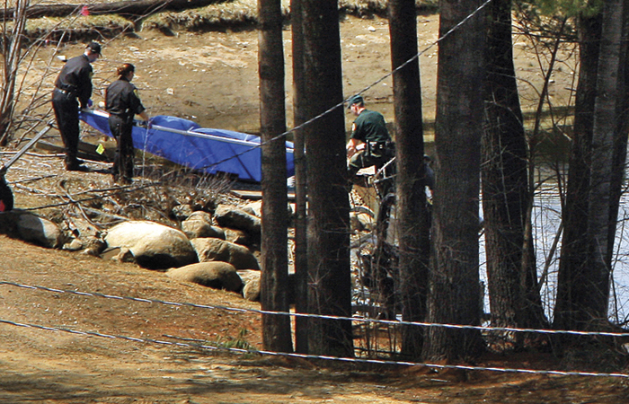 Police remove a tarp from the edge of a snowmaking pond at Mount Cranmore today. Police focused their investigation on the pond, which is near where Krista Dittmeyer's car was found on Saturday morning.