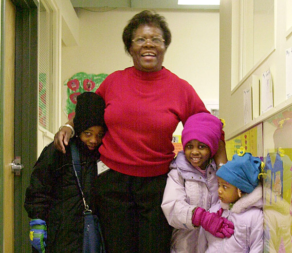A teacher helps young children get ready to go home. Reaching kids this age early can pay dividends for decades.