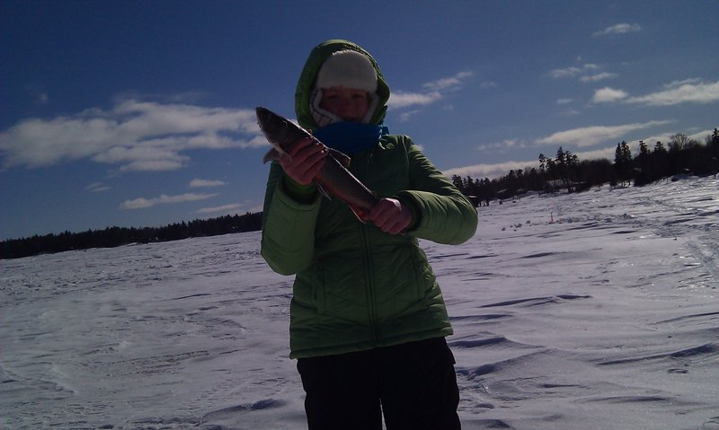 Jillian Beland of Augusta displays a 15-inch brook trout she caught at Moosehead Lake during a family trip in February.