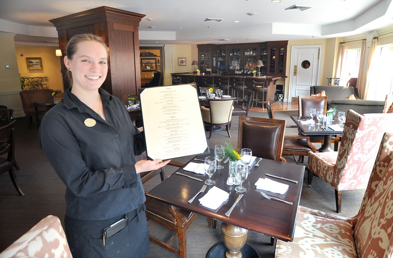 Server Kate Somerville displays a menu at Eve's at the Garden, the restaurant at the Portland Harbor Hotel, where the service is door-to-door attentive.