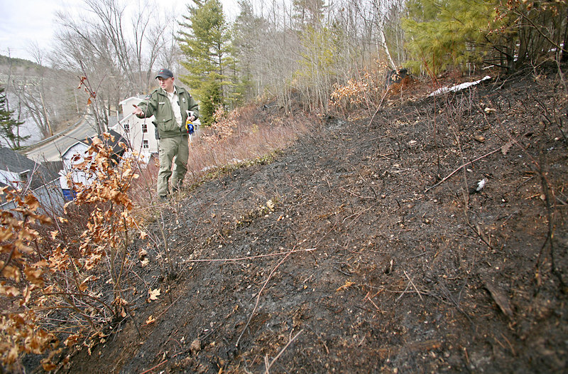 Forest Ranger Matt Bennett investigates the scene of a grass fire that took the life of Frank Hebert, 85, on River Road in Buxton. Hebert was burning grass on an embankment behind his home Wednesday when his clothing caught fire.