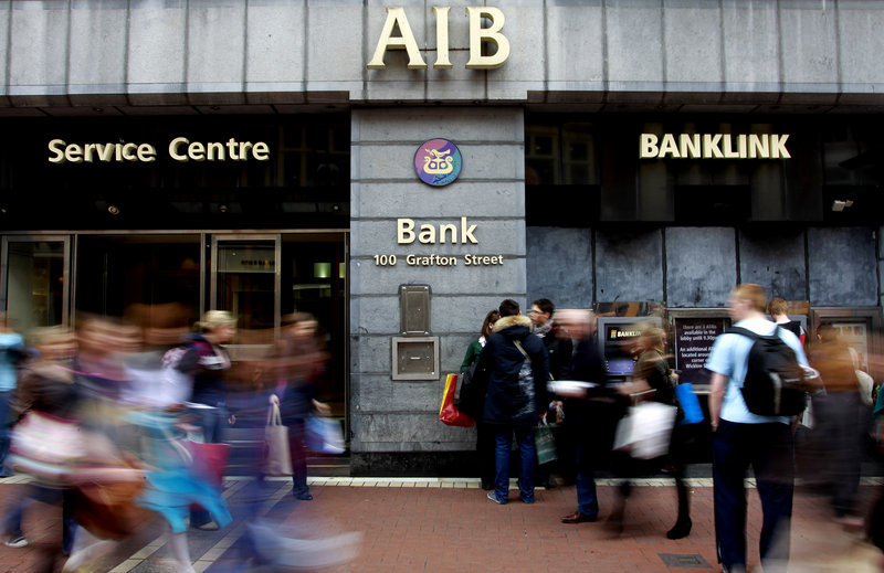 "People wait to use the cash machine Thursday at an Allied Irish Bank in Dublin. The government intends to create ""two pillar banks"" for the financial system, Allied Irish and the Bank of Ireland. The other Irish-owned banks would be dismantled."