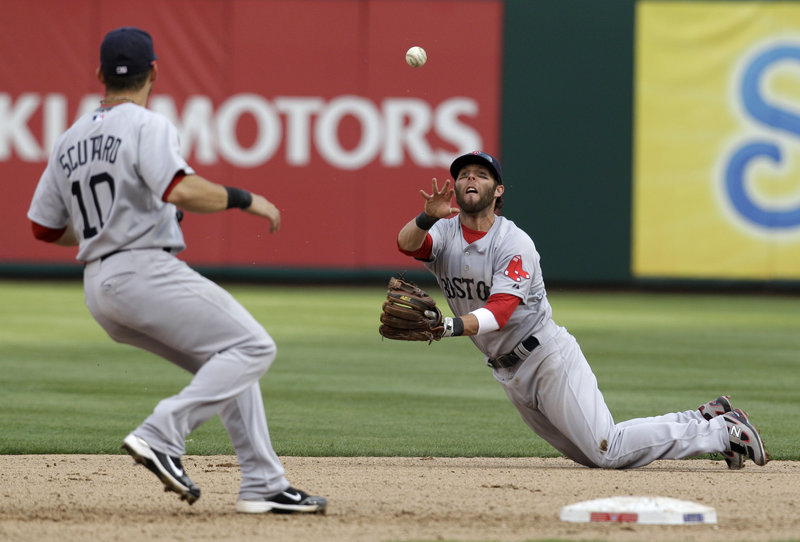 Dustin Pedroia of the Boston Red Sox flips the ball to shortstop Marco Scutaro for a force play at second in the seventh inning Friday. The Red Sox fell to the Texas Rangers, 9-5.