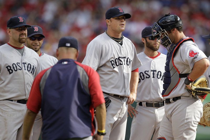 Red Sox pitcher Jon Lester, center, awaits word from manager Terry Francona, foreground left, who removed him from the game in the sixth inning of Boston's season opener Friday against the Texas Rangers in Arlington, Texas. Also pictured are teammates, from left, Kevin Youkilis, Marco Scutaro, Dustin Pedroia and Jarrod Saltalamacchia. The Rangers won, 9-5.
