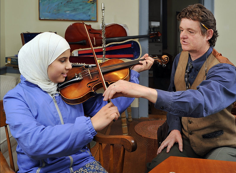 Attorney Peter Lee shows Zahraa Rikan, 15, an Iraqi refugee, how to hold the bow and violin at his office in Yarmouth. Lee collects instruments from donors and loans them to aspiring but cash-strapped kids.