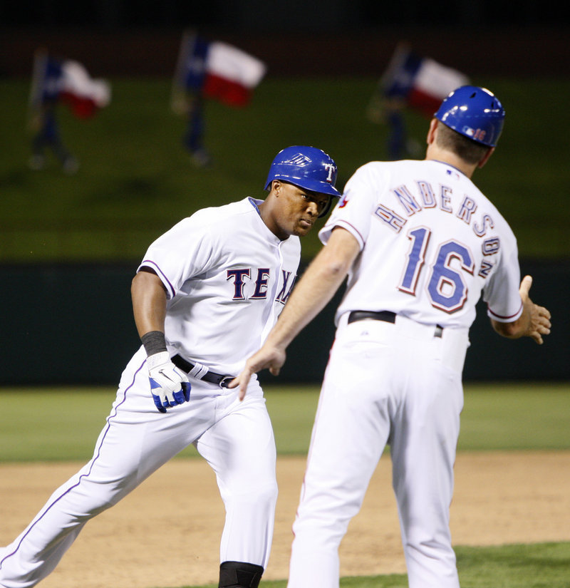 Adrian Beltre of the Texas Rangers receives the way-to-go from third-base coach Dave Anderson after hitting a grand slam Saturday night against the Boston Red Sox.