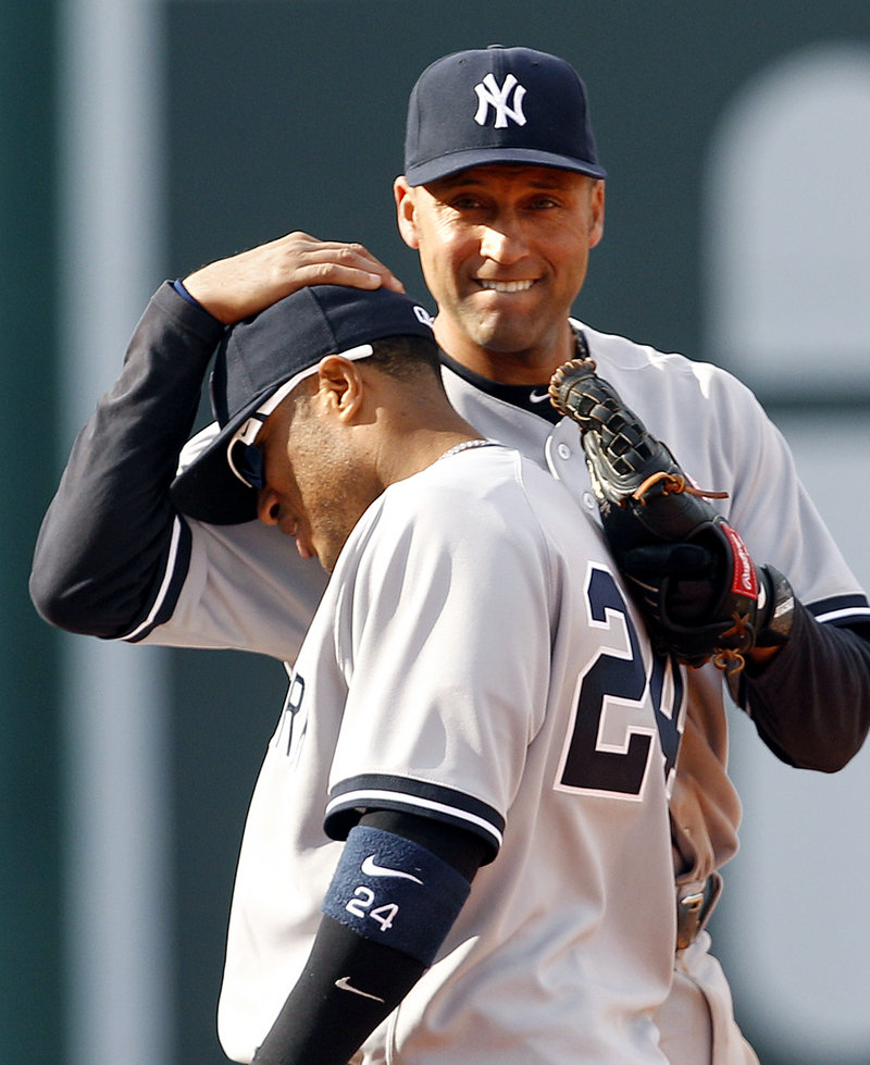 Robinson Cano, who continued his career-long torrid hitting in Fenway Park, receives a pat on the head from Derek Jeter after the New York Yankees came away with a 9-4 victory Saturday over the Red Sox.