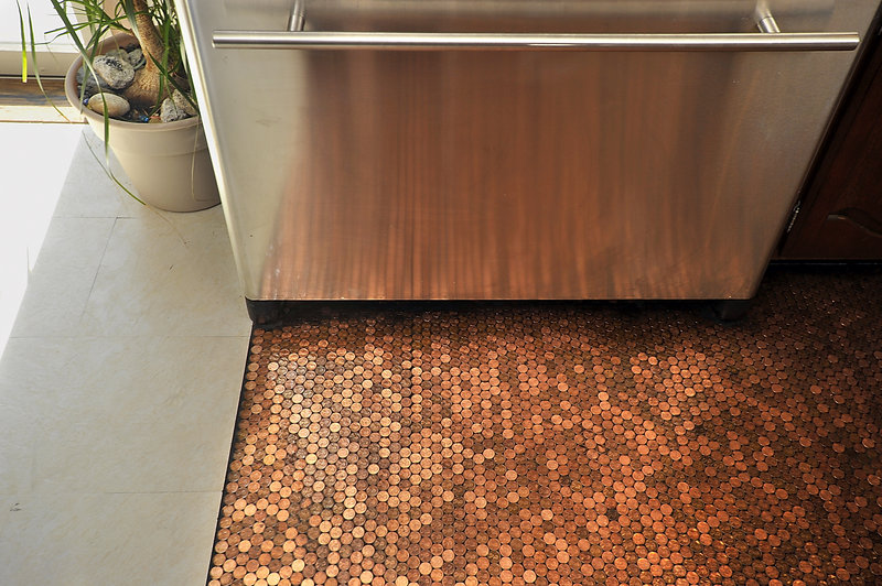 "Edwards' stainless-steel refrigerator reflects the rich coppery patina of the pennies she used to create her kitchen floor. ""When the sun hits it just right, this floor just glows,"" says Edwards."