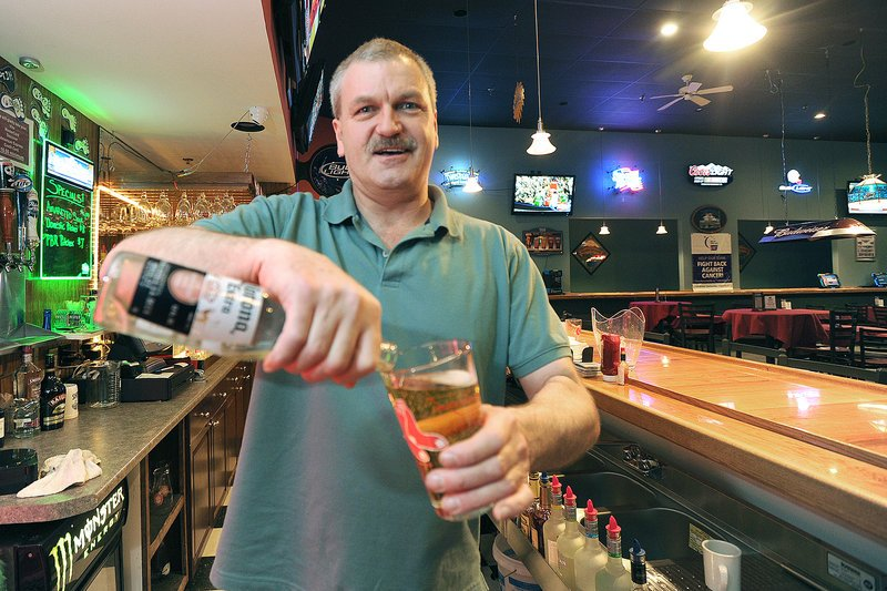 Bartender Mark Ross pours a beer at Club 302 in Windham, a huge gathering spot that's all about charitable causes and events, all the time. It has a scrolling lineup of live music, theater performances, banquets and receptions.