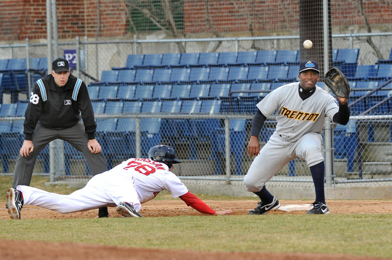 Alex Hassan of the Portland Sea Dogs dives safely back to first base Tuesday night as Myron Leslie of the Trenton Thunder awaits the throw. Hassan went 3 for 5 with a double, driving in two runs, and improved his batting average to .500 during the 7-0 victory at Hadlock Field.