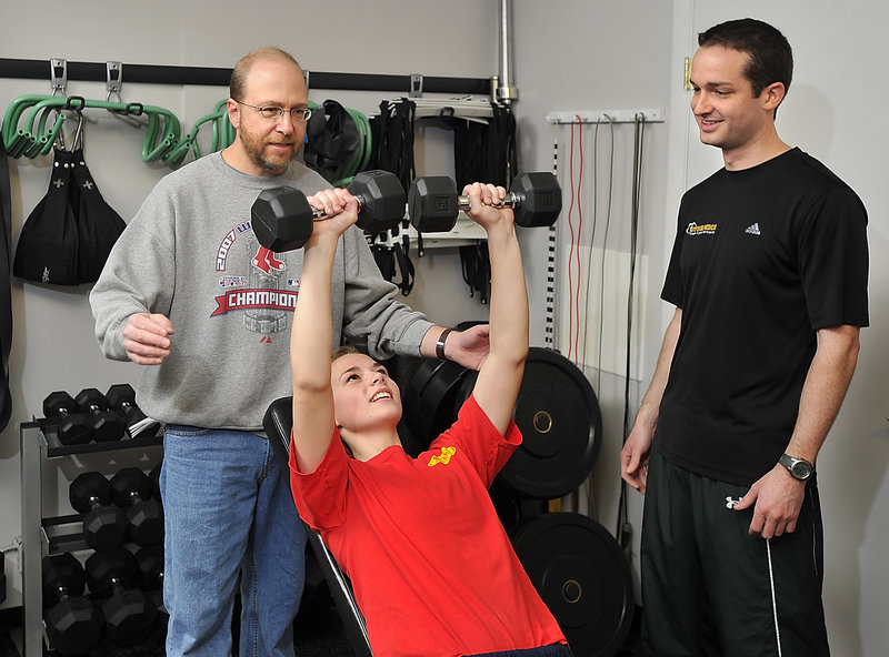 Ray Routhier, left, serves as a spotter for Phoebe Shields of Cape Elizabeth under the guidance of James Hollenkamp, a personal fitness trainer in Portland.