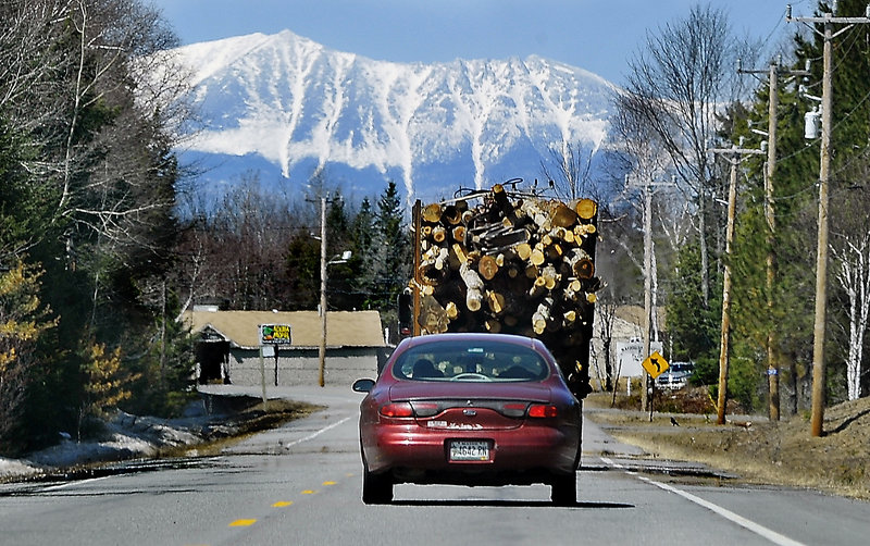 Mount Katahdin looms in the distance as a truck carries logs to a logging yard in Millinocket in 2014. On Saturday, close to 1,000 runners are expected for an unusual road race that aims to help the struggling mill town.