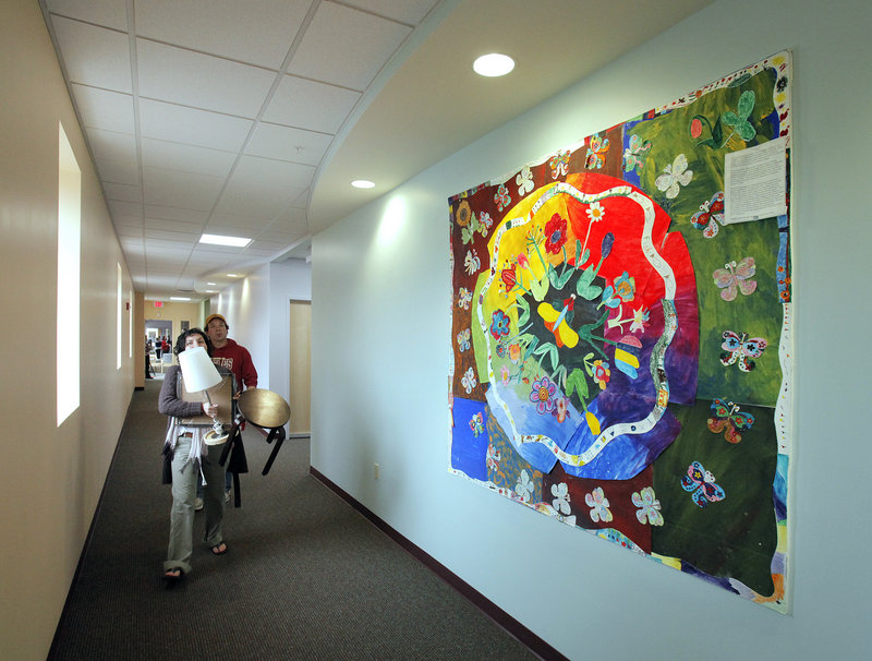 Allegra Hirsh, a counselor with Community Counseling Center, carries furnishings to her office Monday at the center's new location at 165 Lancaster St. The wall art, called The Butterflies of Spring, was made by members of the Elderworks program.