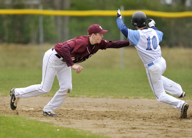 Windham's Cody Dube, left, tags out Westbrook's Joe Quinlan on a steal attempt in the bottom of the first inning Monday afternoon in Westbrook. The Blue Blazes opened with a 3-0 victory.