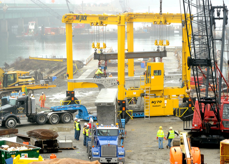 A travel lift unloads large precast concrete bridge segments at the site of the new bridge over the Fore River in Portland. The old bridge will remain open during the construction process, which is expected to last into the summer of 2012.