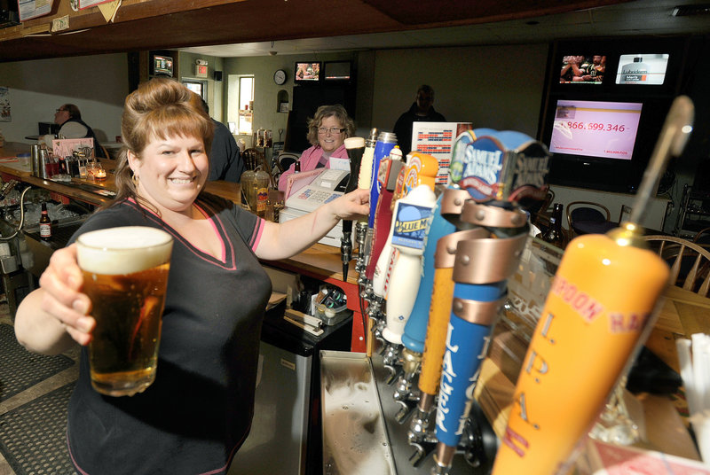 Bartender Sue Hanna pours a draft beer at Spectators Sports Bar in Sanford. The full bar has almost 60 kinds of beer, affordable food, plenty of games, a variety of live entertainment and 13 TVs.