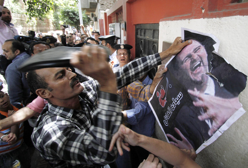 A Syrian man beats a poster of President Bashar al-Assad with a shoe during a protest Tuesday at the Syrian Embassy in Cairo, Egypt. Human rights groups say at least 35 people have died in the past two days in an onslaught by Syrian forces.