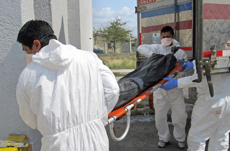 Employees unload a body from a refrigerated truck last week at the city morgue in Matamoros, Mexico. Families of those feared abducted and killed by the Zeta drug cartel have taped photocopied fliers of their loved ones to the walls of state forensic offices there, hoping the bodies can be identified.