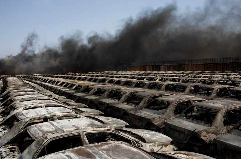Black smoke drifts over rows of burned cars at the port of Misrata, Libya, Wednesday. The port was quiet after fierce bombardment and attacks the day before.