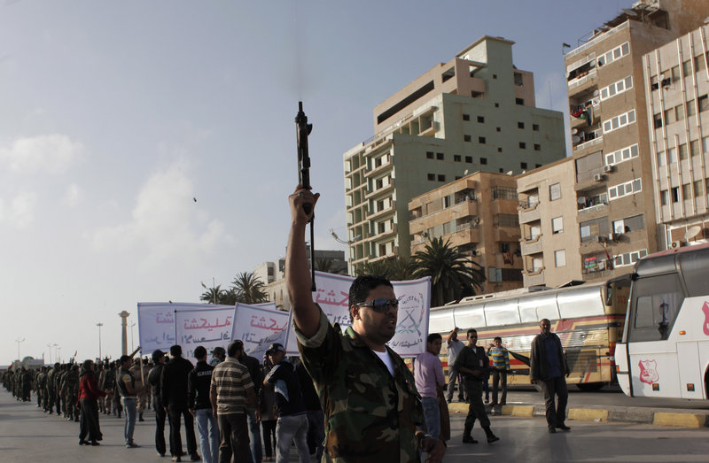 A Libyan rebel fires his machine gun in the air during a military parade Wednesday in Benghazi, Libya. Participants called for more Western arms for the anti-Gadhafi revolution but rejected intervention on the ground by foreign troops.