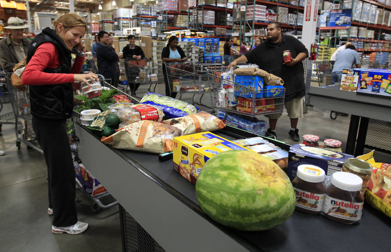 Shoppers load a conveyor belt at a checkout counter at Costco in Mountain View, Calif. Americans saw their incomes rise last month, but analysts say most of the extra money went toward covering higher prices for gas and food.
