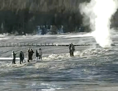 A group of tourists takes photos dangerously close to the Old Faithful geyser in Yellowstone National Park in Wyoming on Wednesday, in this still made from National Park Service video. They were fined by park rangers.