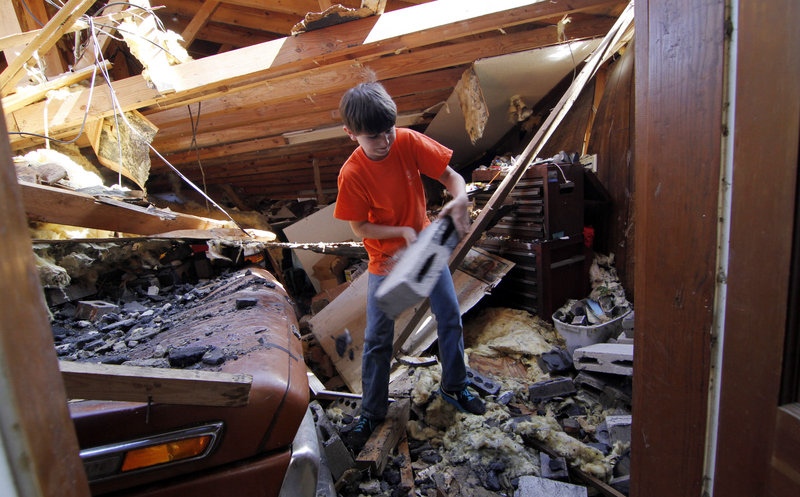 Bryton Frost, 10, tosses aside debris in his grandfather's wrecked garage Friday in Hackleburg, Ala. Survivors of the deadliest tornado outbreak since the Great Depression endured blackouts and long lines for gas as they began digging what possessions they could find from the rubble.