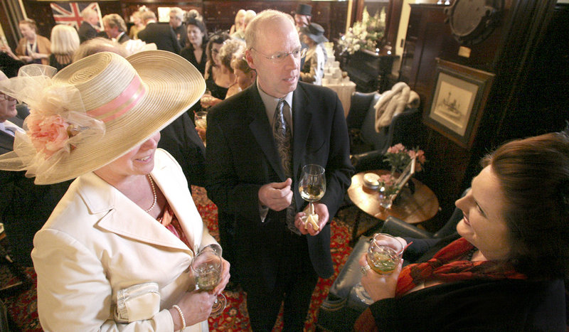 Jo Harrison of Brunswick, left, and her husband, Leigh, visit with Cecille Tetrev of Woolwich during a black tie formal party to celebrate the royal wedding at the Cumberland Club in Portland on Friday. Props included magazines and books on the British royals, and a giant poster with pictures of past monarchs and their offspring.