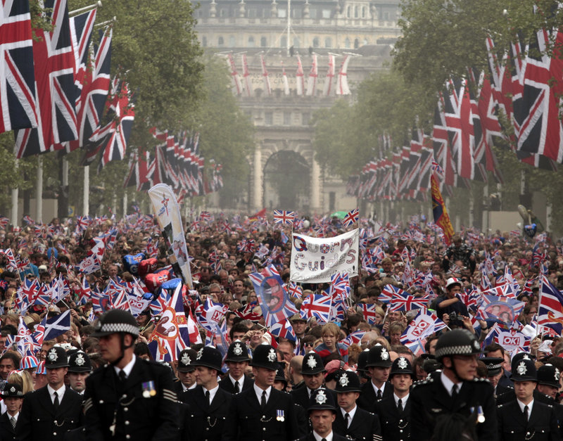 Throngs of spectators make their way down the Mall to Buckingham Palace after the wedding Friday. An estimated million people lined the route between the palace and Westminster Abbey to see the bridal couple and the royal family pass by.