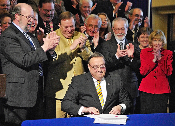 Gov. Paul LePage, is applauded after signing the ambitious GOP health insurance reform bill, L.D. 1333. into law today. About 75 Republican lawmakers stand behind him in the Hall of Flags at the State House. Standing immediately behind him, from left, are: Speaker of the House Bob Nutting, R-Oakland; Senate President Kevin Raye, R-Perry; Rep. Wes Richardson, R-Warren; Sen. Rodney Whitemore, R-Skowhegan; Rep. Joyce Fitzpatrick, R-Houlton; and Sen. Lois Snowe-Mello, R-Poland.