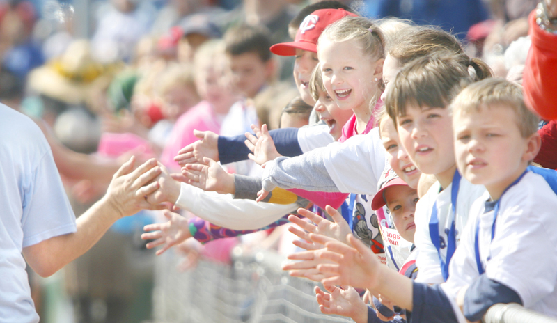 Kids slap hands with runners along the third-base line near the finish line at Hadlock Field during the Mothers' Day 5K sponsored by the Sea Dogs.