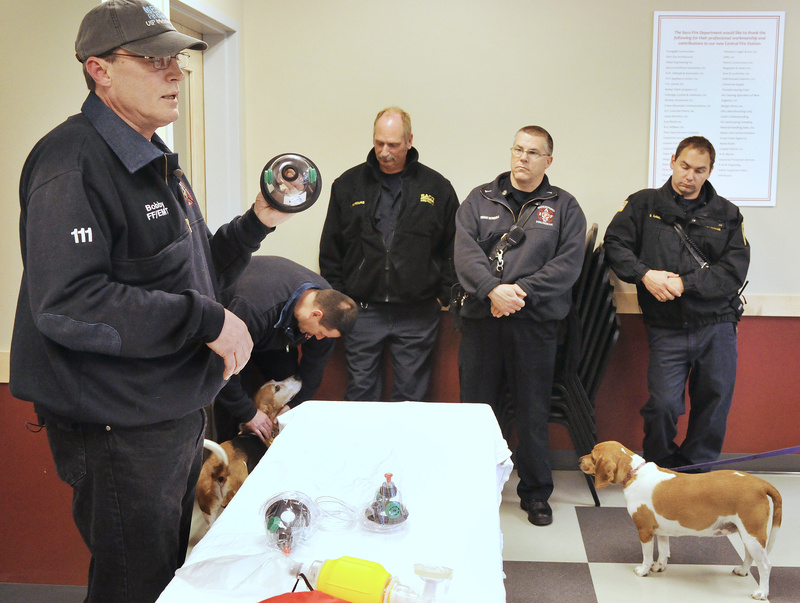 """MAN'S BREATH FRIEND? – Bobby Silcott, an animal control officer in Naples, demonstrates the use of pet oxygen masks to members of the Saco and Biddeford fire and rescue departments this week. Silcott was able to donate six masks to each department thanks to a donation from Invisible Fence of Southern Maine and Seacoast New Hampshire. Silcott tried to demonstrate the use of the mask on his dog Elvis during the demonstration, but """"Release Me"""" seemed to be the only tune on Elvis' mind. With the oxygen masks, firefighters and rescuers can often save the life of a pet that has been removed from a burning building and may be suffering from smoke inhalation."""