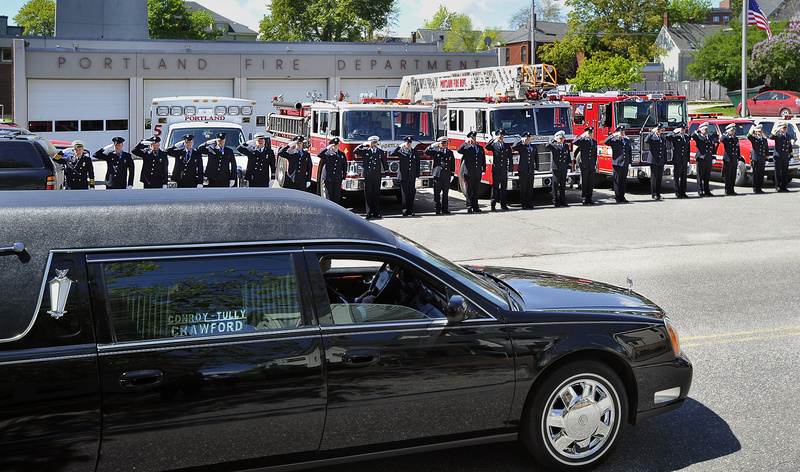 Firefighters salute Wednesday as the funeral procession for James P. Fox stops at the Bramhall Station on Congress Street. Fox, who had Down syndrome, was named the department's honorary deputy chief in 2003.