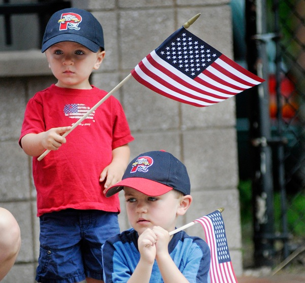 Reid Haile , 2, left, and Henry Haile 5, of Westbrook wave their flags as they watch veterans march along Congress St. During the Memorial Day Parade in Portland Monday, May 30, 2011.