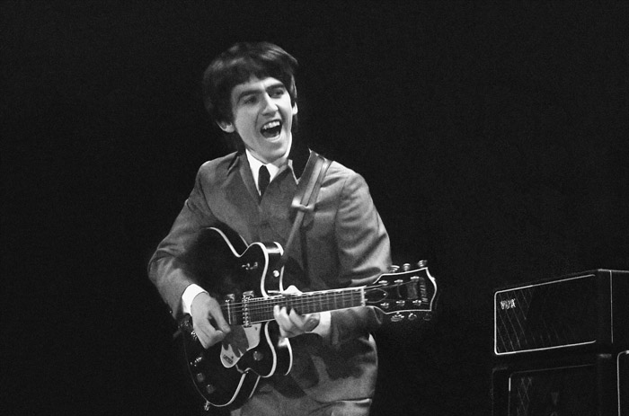 This Feb. 11, 1964, of George Harrison at the Washington Coliseum in Washington, D.C. The concert photos, taken when photographer Mike Mitchell was just 18 years old, will be auctioned by Christie's.