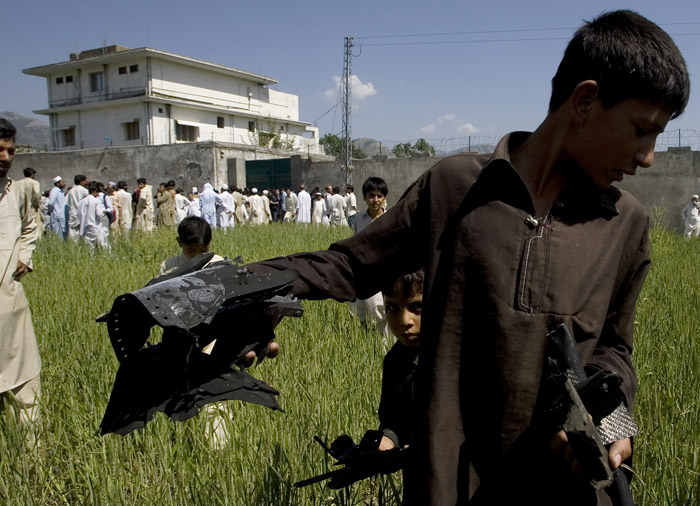 A Pakistani youngster shows metal pieces collected today from a wheat field outside the house, in background, where al-Qaida leader Osama bin Laden was killed in Abbottabad, Pakistan. Local residents showed off small parts of what appeared to be a U.S. helicopter that Washington said malfunctioned and was disabled by the American commando strike team as they retreated.
