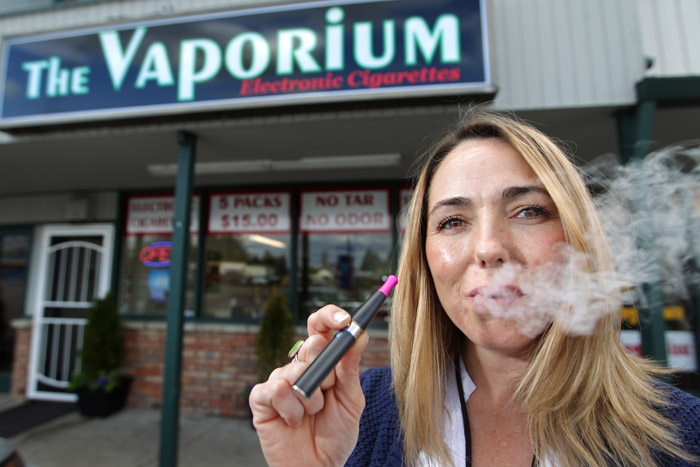 Kim Thompson, owner of a new business called The Vaporium in Lakewood, Wash., exhales vapor from one of the smokeless cigarette devices now on the market. The patent purchased by Philip Morris uses an aerosol system to deliver nicotine more rapidly to mimic the nicotine